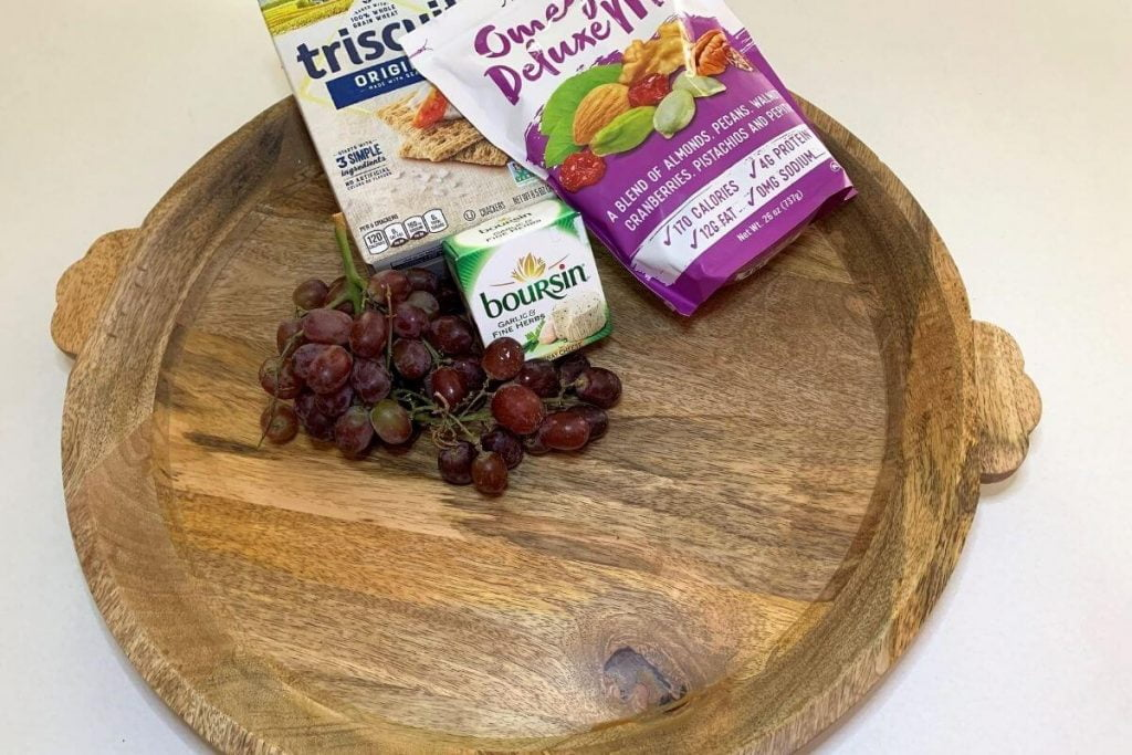 large round wooden charcuterie board grapes crackers cheese trail mix