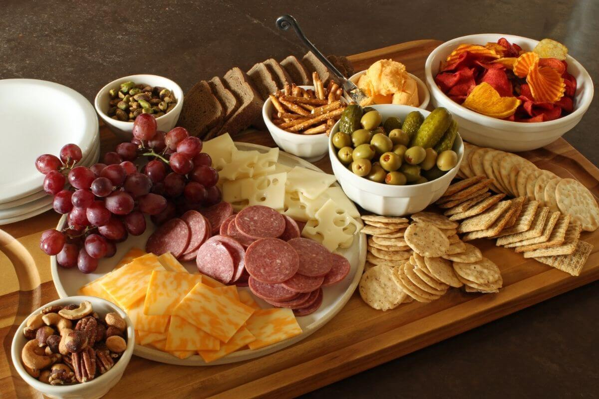 rectangular wooden charcuterie board with dishes of snacks