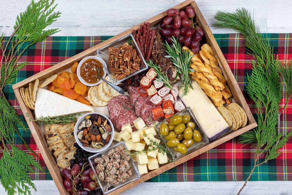 rectangle holiday charcuterie tray with variety of snack foods on a green and red plaid placemat with fresh greenery to decorate