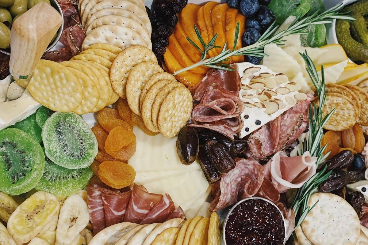 close up of charcuterie board with crackers meats cheese pickles kiwi banana jelly figs and rosemary garnish
