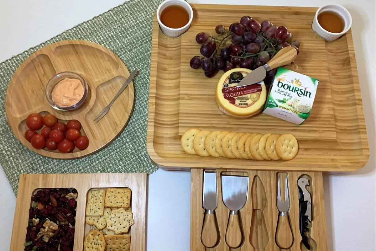 large wooden multi piece charcuterie with variety of foods
