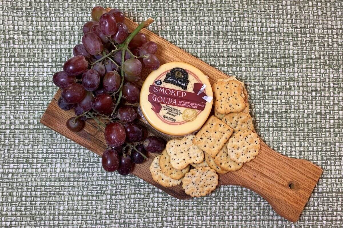 wooden cutting board type charcuterie with grapes cheese crackers