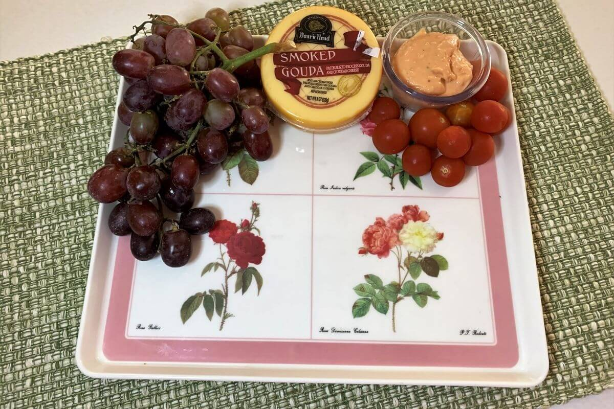 pink and white floral platter with grapes cheese cherry tomatoes and dip