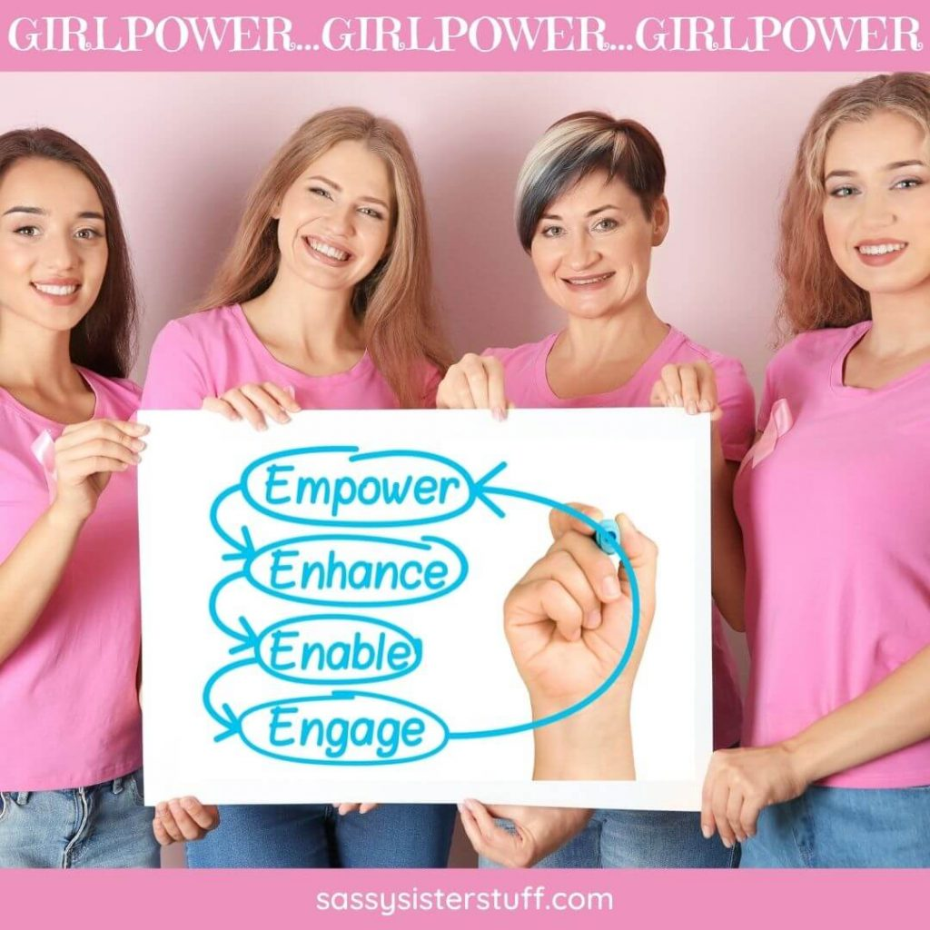 four happy ladies in pink shirts showing a sign for empowerment and girlpower