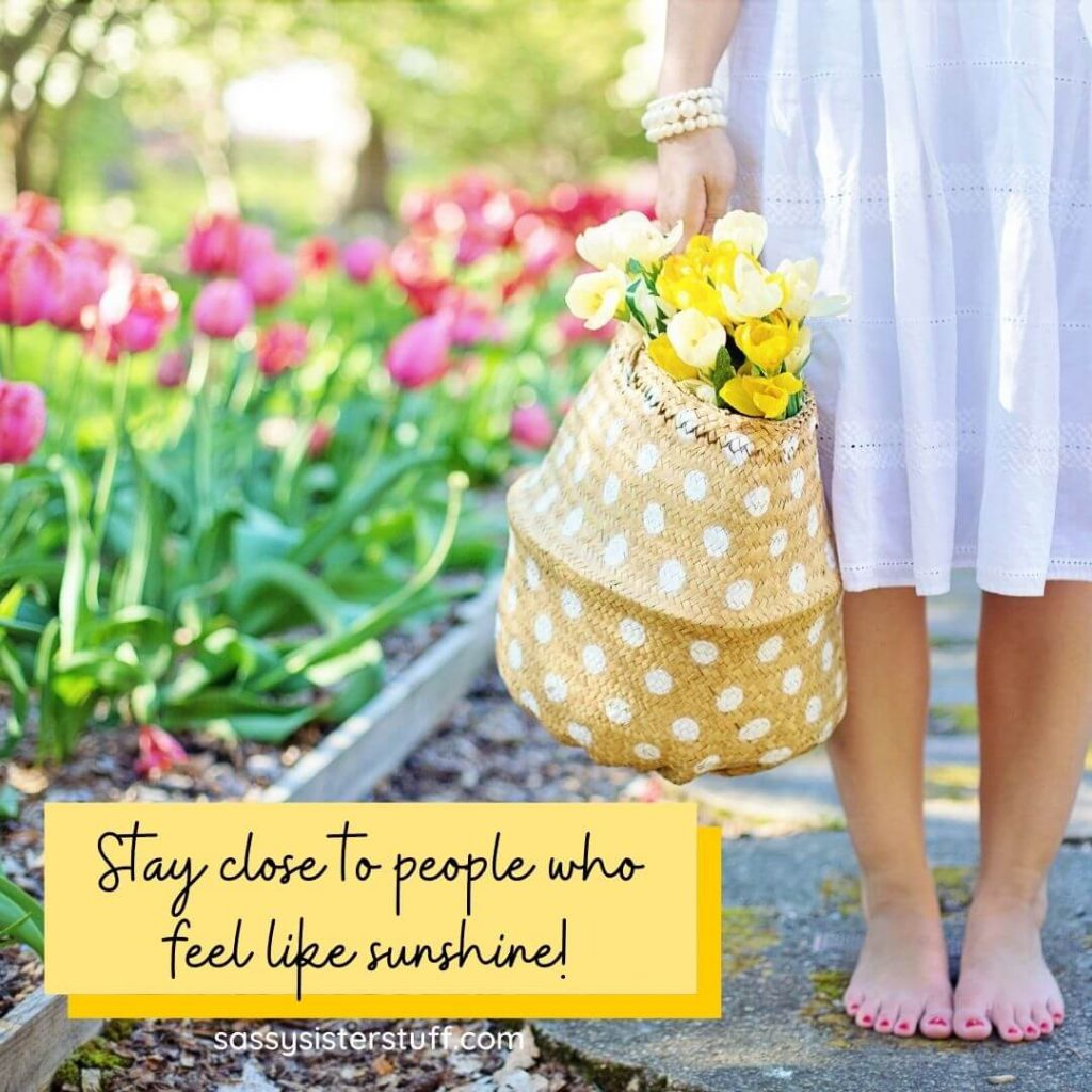 pink tulips a women in a white dress holding a yellow bag with yellow tulips in it and a quote about people who make you feel like sunshine