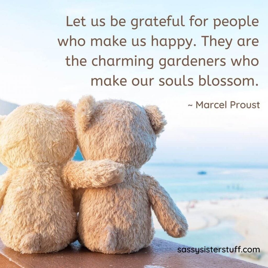 two tan teddy bears sit at the edge of the with arms around each other and a quote about being grateful for people who make us happy