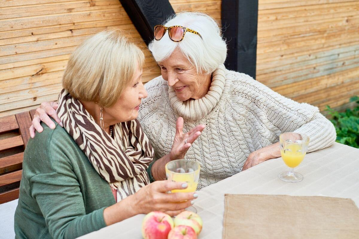 two happy older ladies sit together at a table socializing