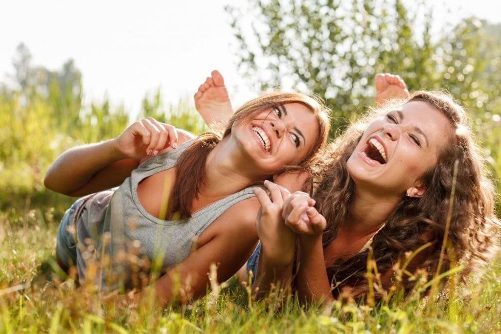 two happy young ladies lay in the grass socializing and laughing