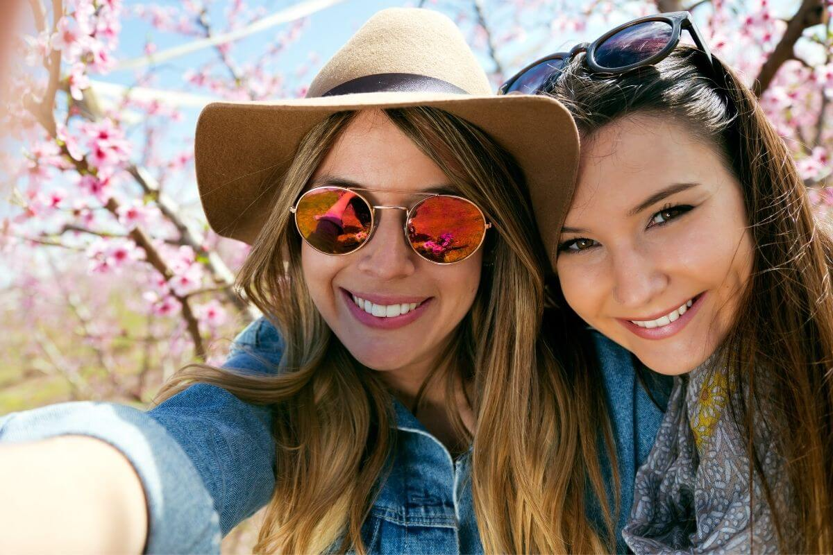 two happy young ladies head to head take a selfie