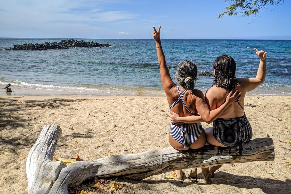 two ladies sit on driftwood on the beach looking out onto the ocean with their arms around each other