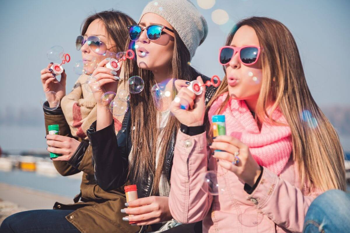 three young ladies enjoy positive social interactions as they blow bubbles together
