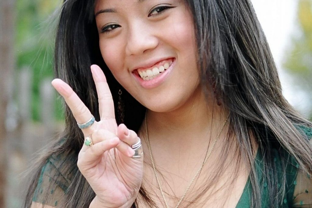 happy woman holds up two fingers for a peace sign