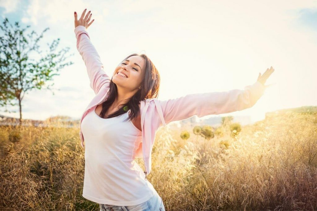 a happy woman stretches in the sunlight in a field
