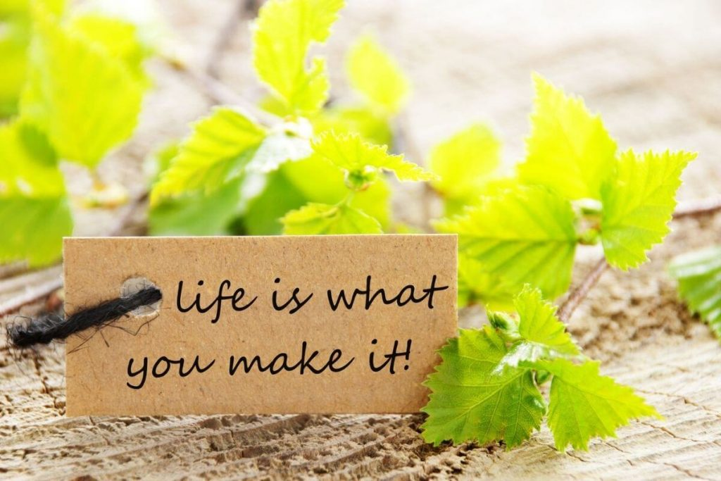 a note that says life is what you make it laying in some green leaves