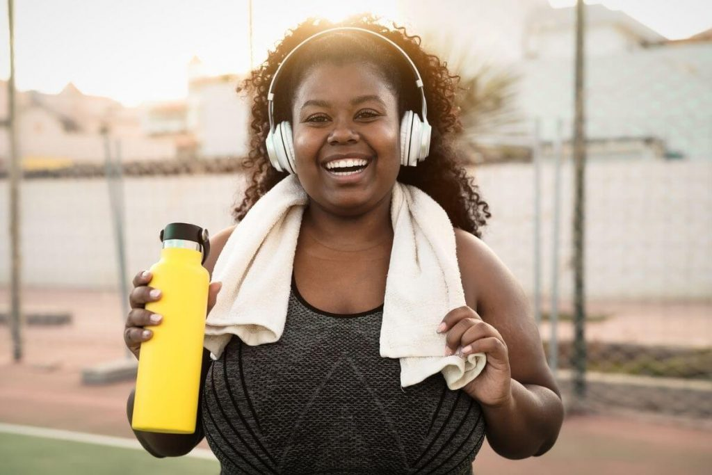 a very happy woman smiles at the camera with headphones a towel and water bottle after exercising
