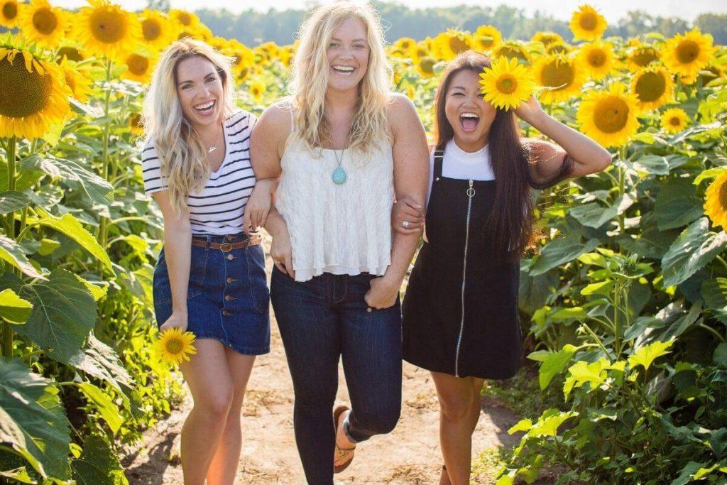 three happy women scroll through a sunflower field