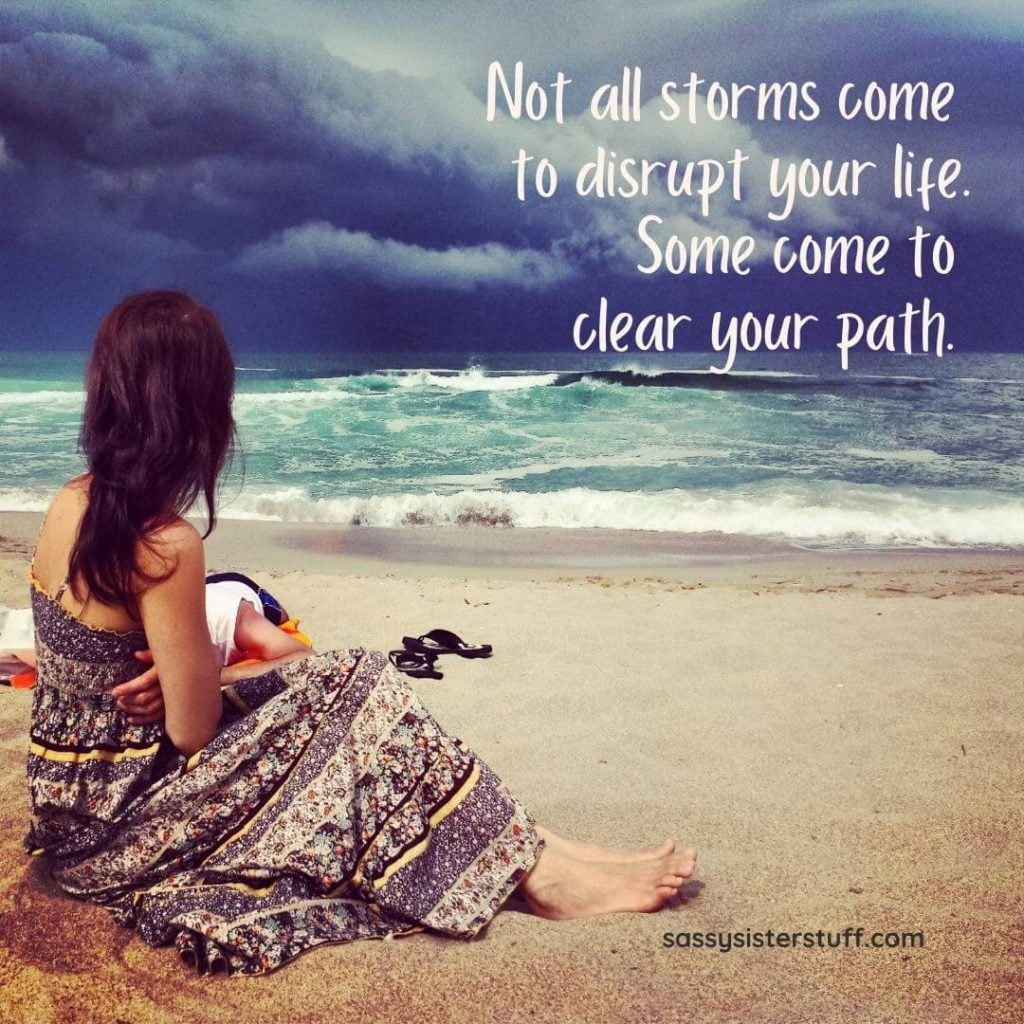 a woman sits on a beach with a storm in the distance and an inspirational quote