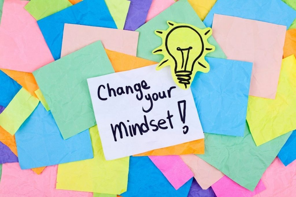 post it notes scatters about with a lightbult cutout and change your mindset note