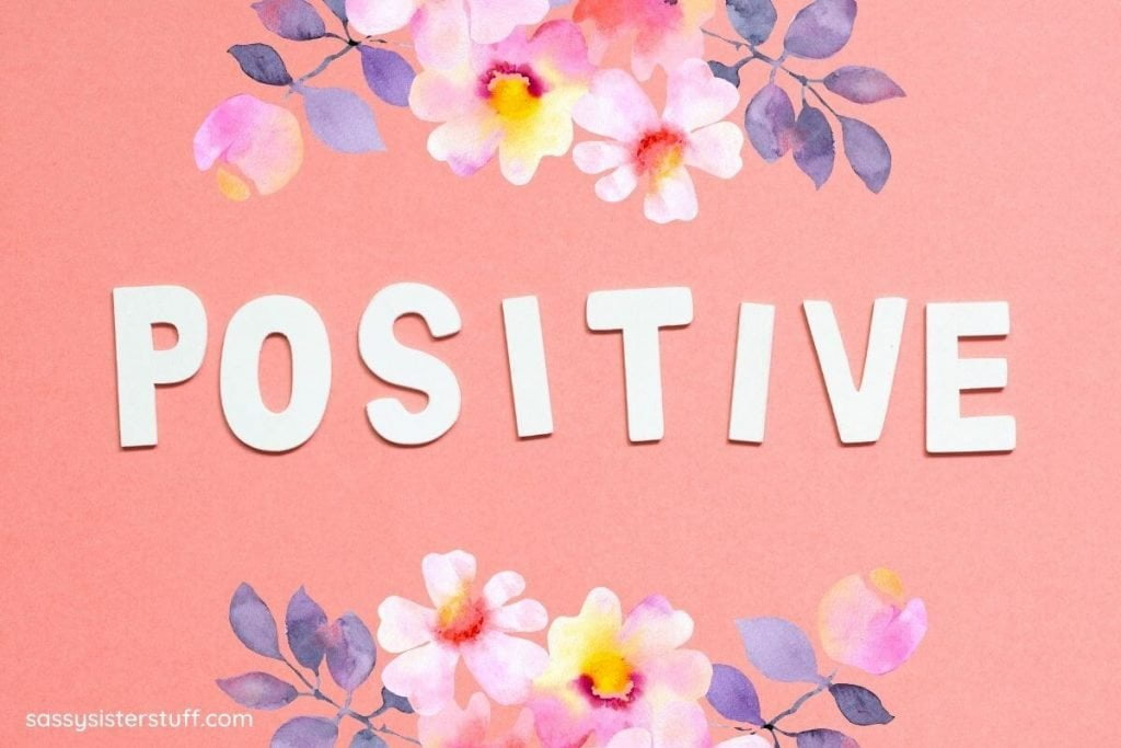 white letters spell positive on a peach background with flowers at the top and bottom of the image