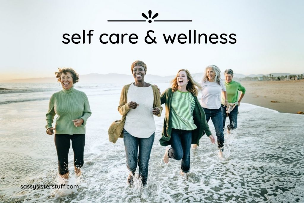 five happy women running on the beach for self care and wellness