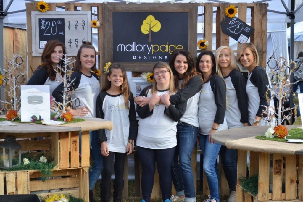 employees from Mallory Paige designs stand at their trade fair display with their products