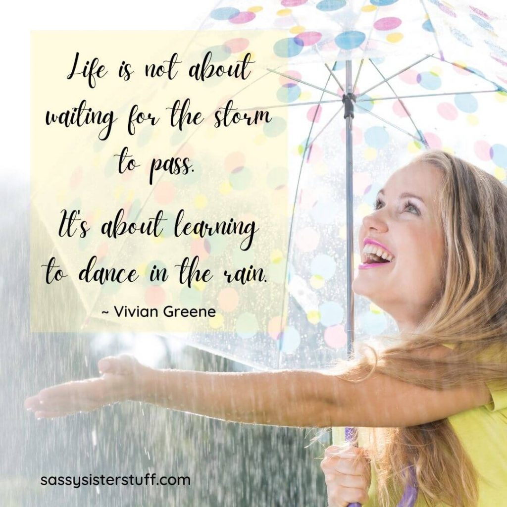 woman smiling under and umbrella reaching out smiling at the rain and a positivity quote
