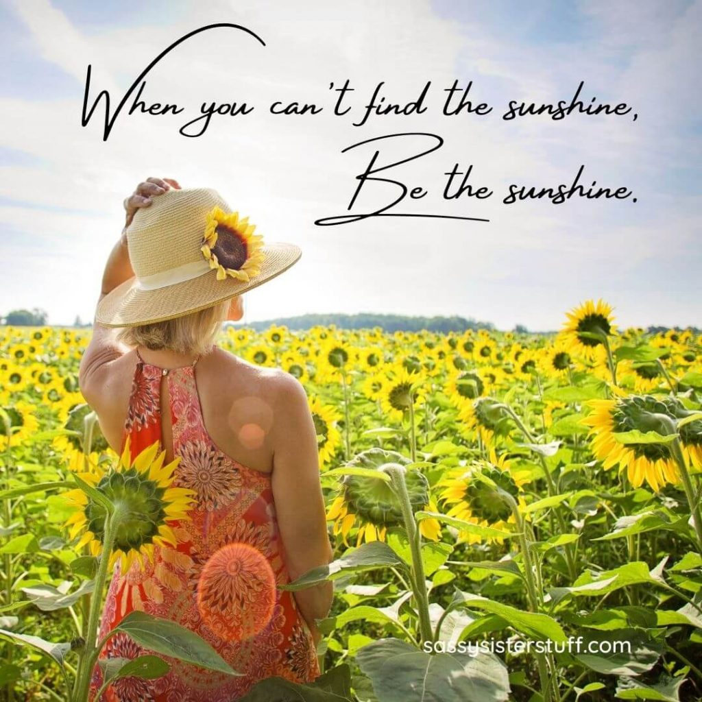 woman standing in a sunflower field with a positivity quote