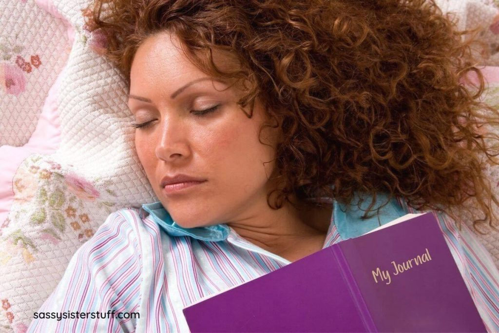 woman has fallen asleep with a journal on her chest