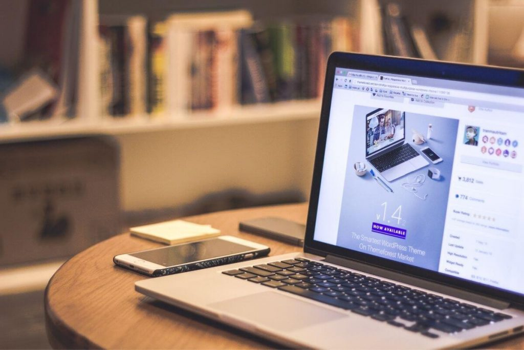 open laptop with wordpress design on it and bookshelves in the background