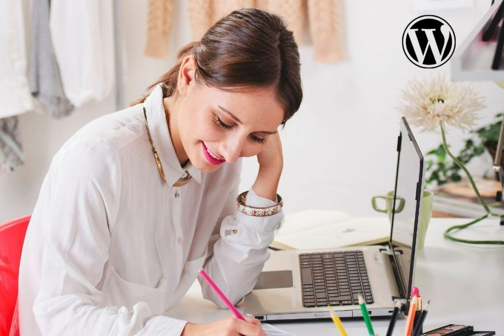 happy lady working at a desk with a laptop in front of her