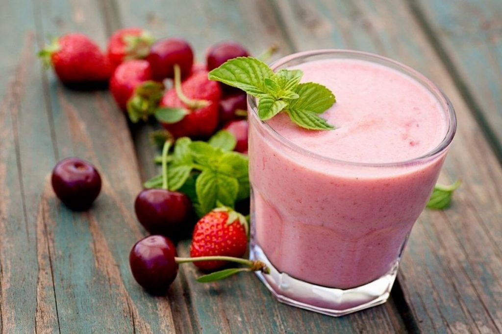 a berry smoothie with fresh berries laying next to the glass for a healthy breakfast