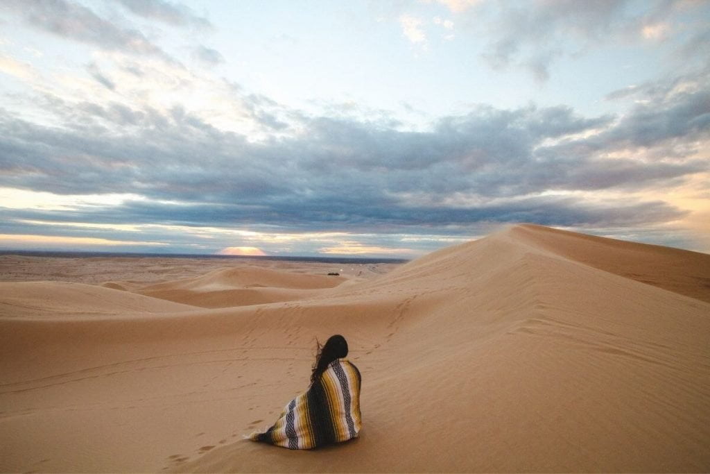 a traveler sits on a sand dune in the desert against a beautiful blue sky