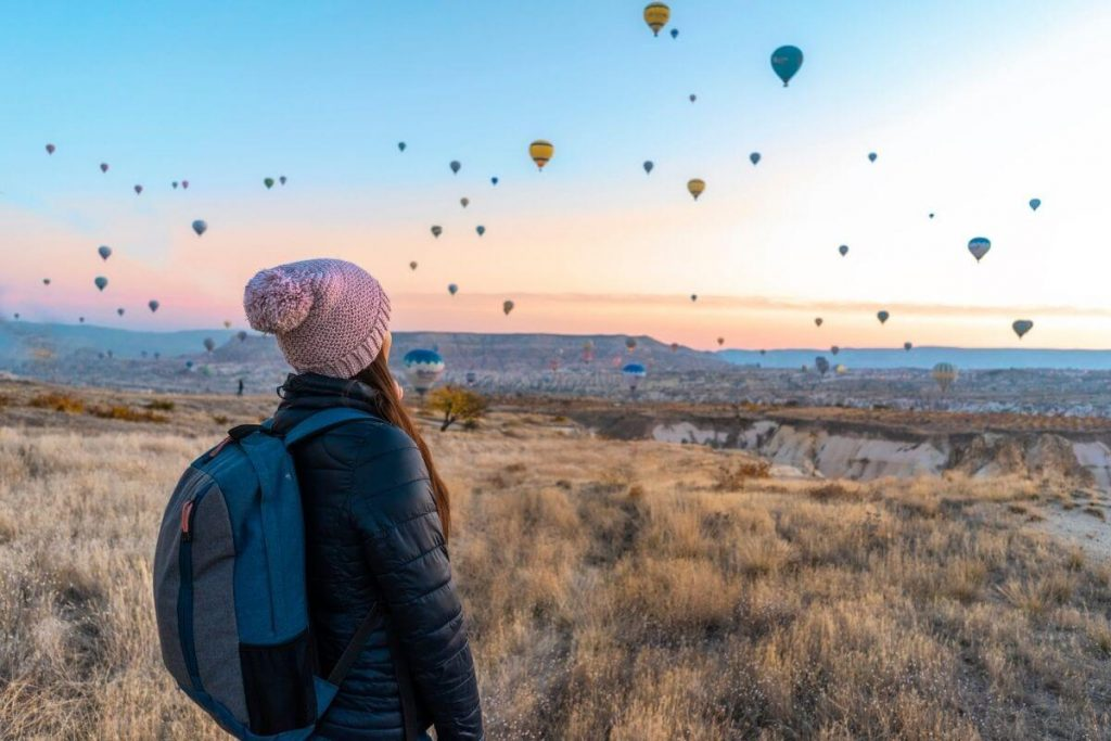 traveler with a backpack on is standing on a hillside looking at dozens of hot air balloons in the sky