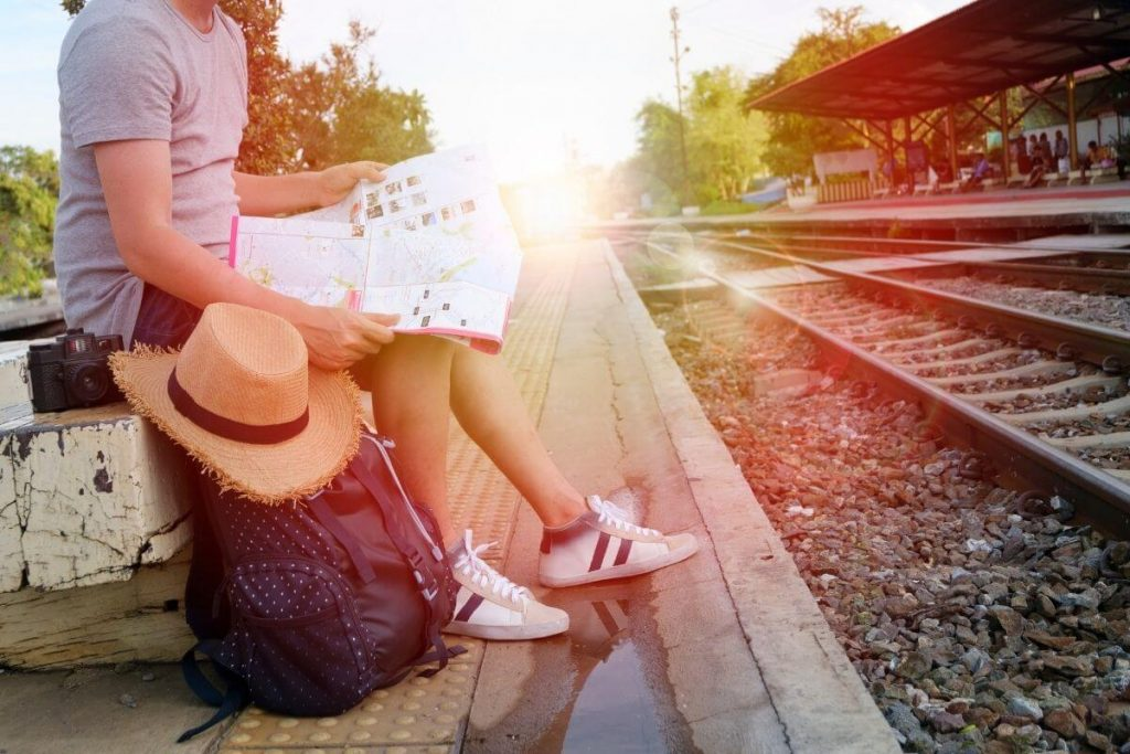 woman with travel bags sits at railroad staiong looking at a map waiting for a train