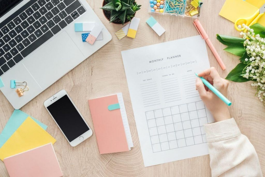 desktop with supplies and woman working on self improvement tasks