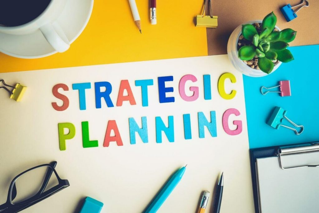 bright papers and desk supplies laying on a desk with strategic planning spelled out in different colored stickers
