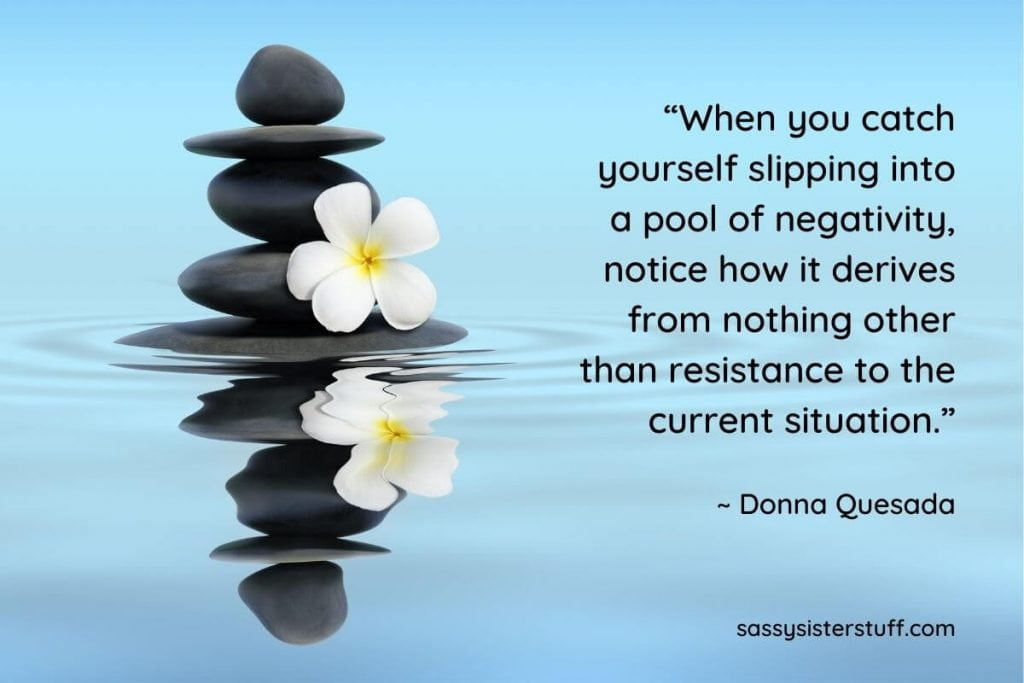 five black rocks stacked on top of each other in a blue pool of water with a white lily and a quote about positivity