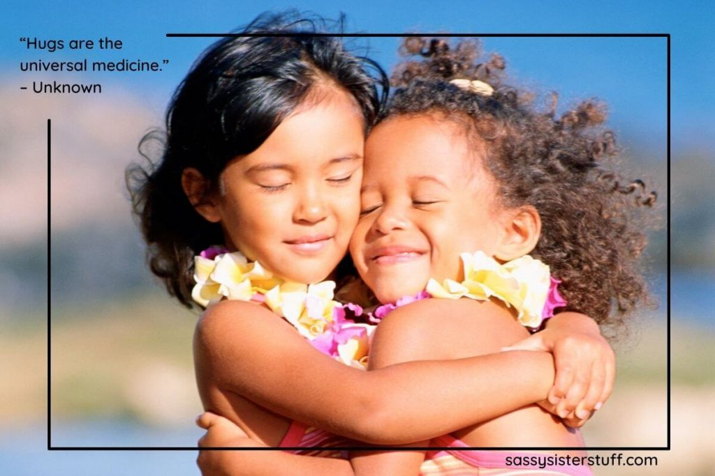 two little girls hugs with smiles on their faces