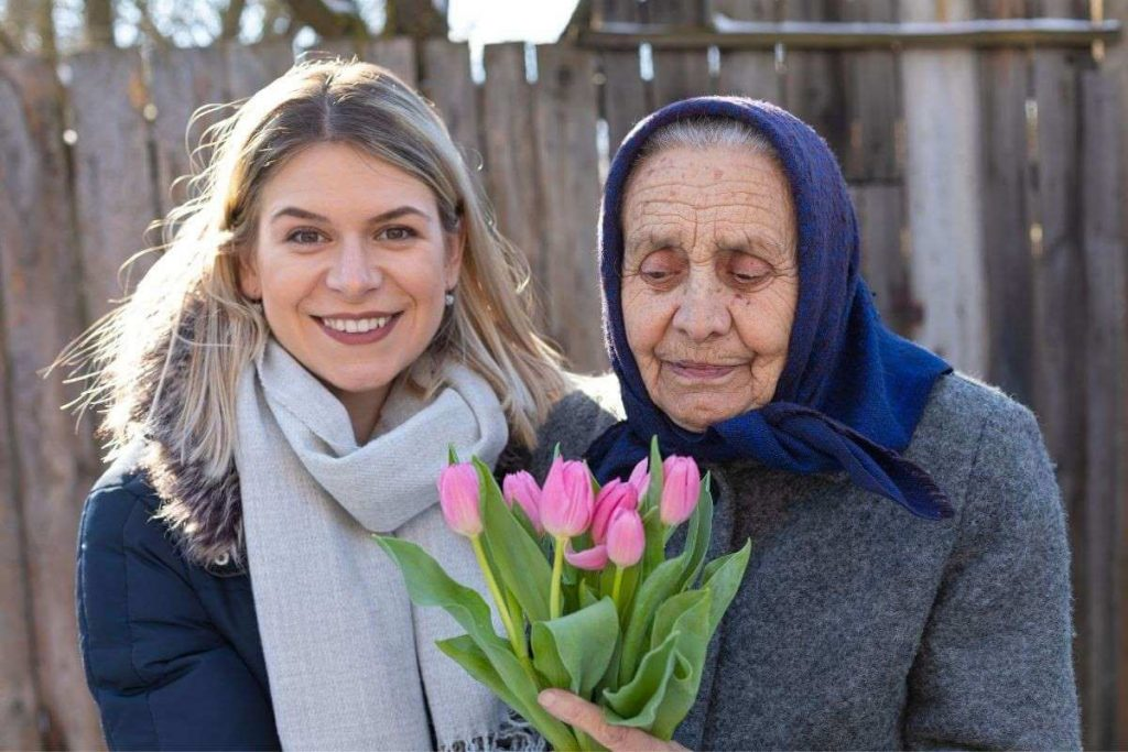 younger and older woman holding a bouquet of flowers with a heart of gratitude