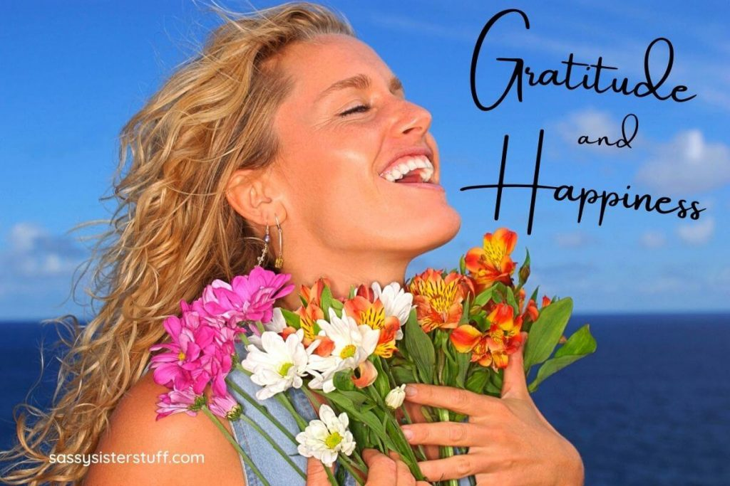 happy and grateful woman at the ocean holding a bouquet of flower