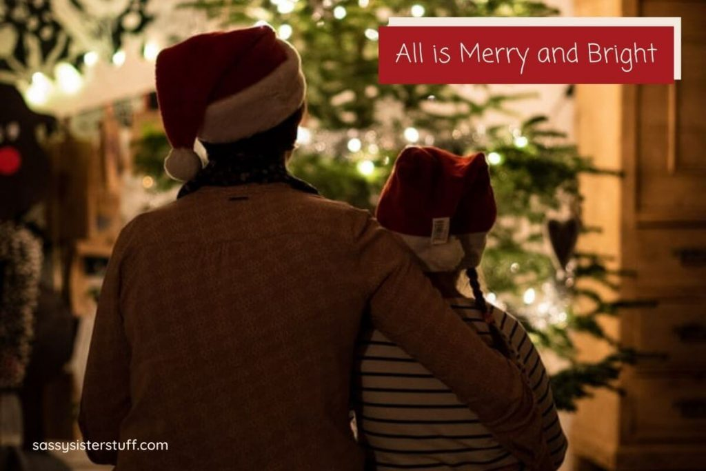 a parent and child sitting in a dark room look at a beautiful Christmas tree after getting organized for the holidays and relaxing together