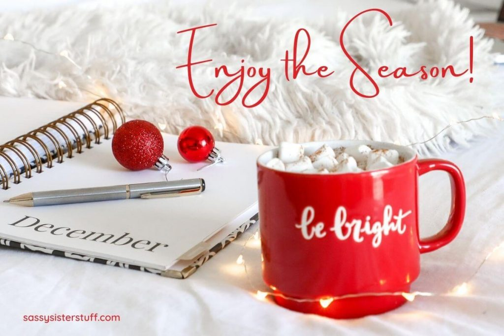 a December journal and pen with hot chocolate in a red mug that says be bright and red letters saying enjoy the season