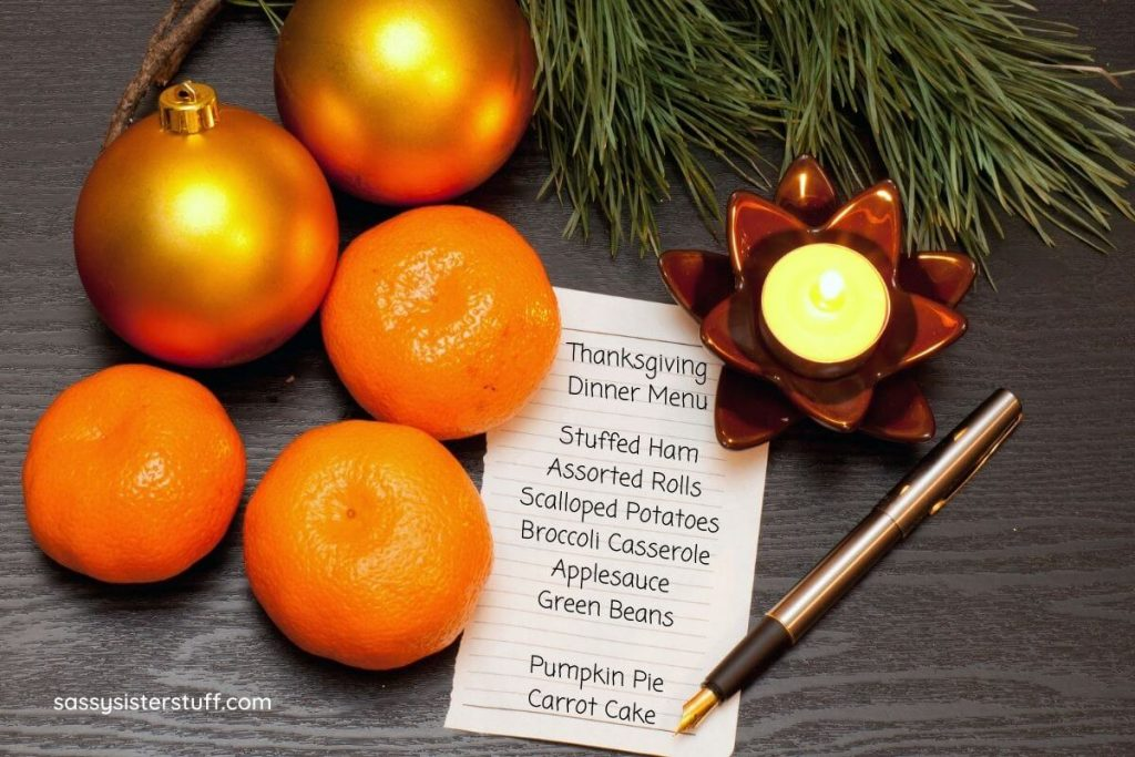 oranges a pine branch and a candle with a list that says Thanksgiving Dinner Menu