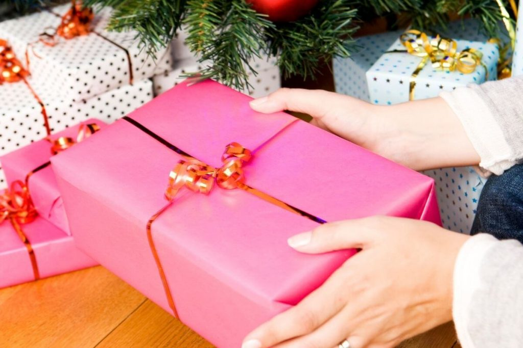 a woman is getting organized for the holidays by putting wrapped gifts under the tree