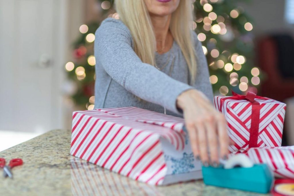 a woman with blonde hair wraps Christmas gifts