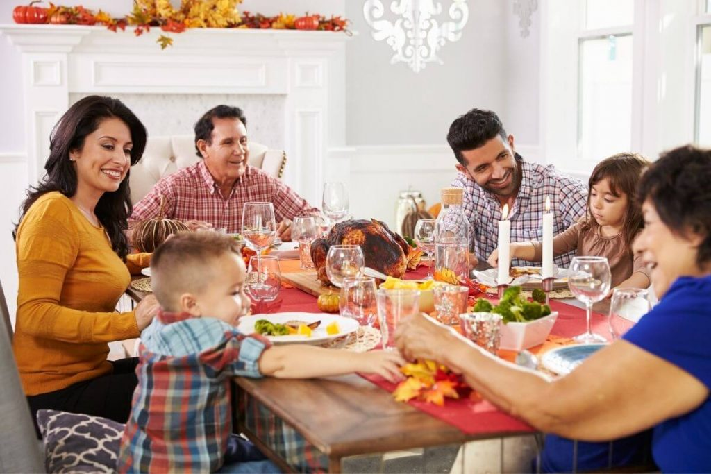 a multi-generational family sharing a simple Thanksgiving dinner of turkey and sides