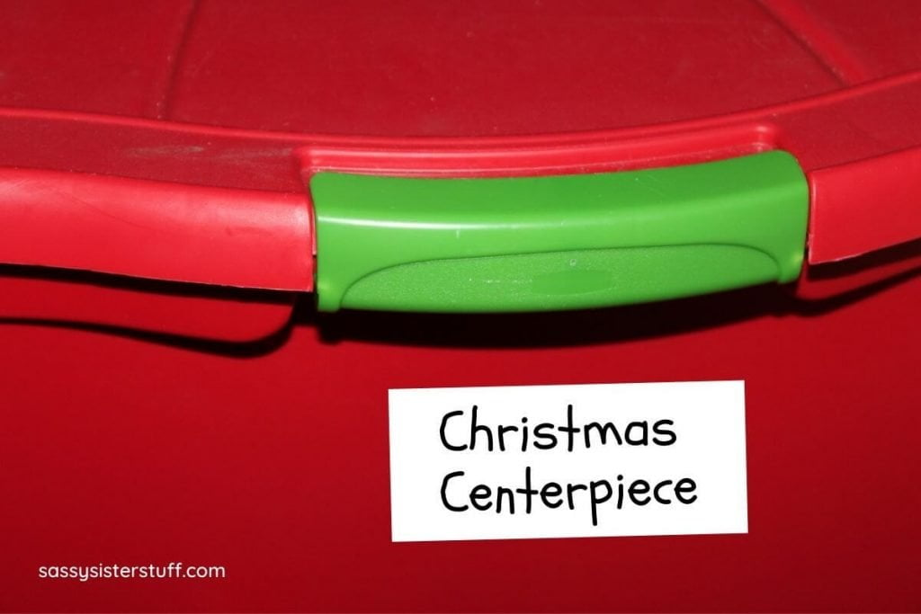 a red and green bin labeled Christmas centerpiece showing how someone is getting organized for the holidays