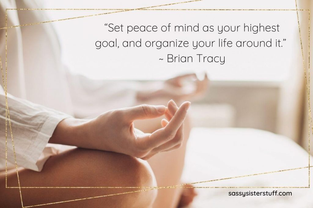 woman sitting on a bed doing yoga with a quote about organizing your life around your peace of mind