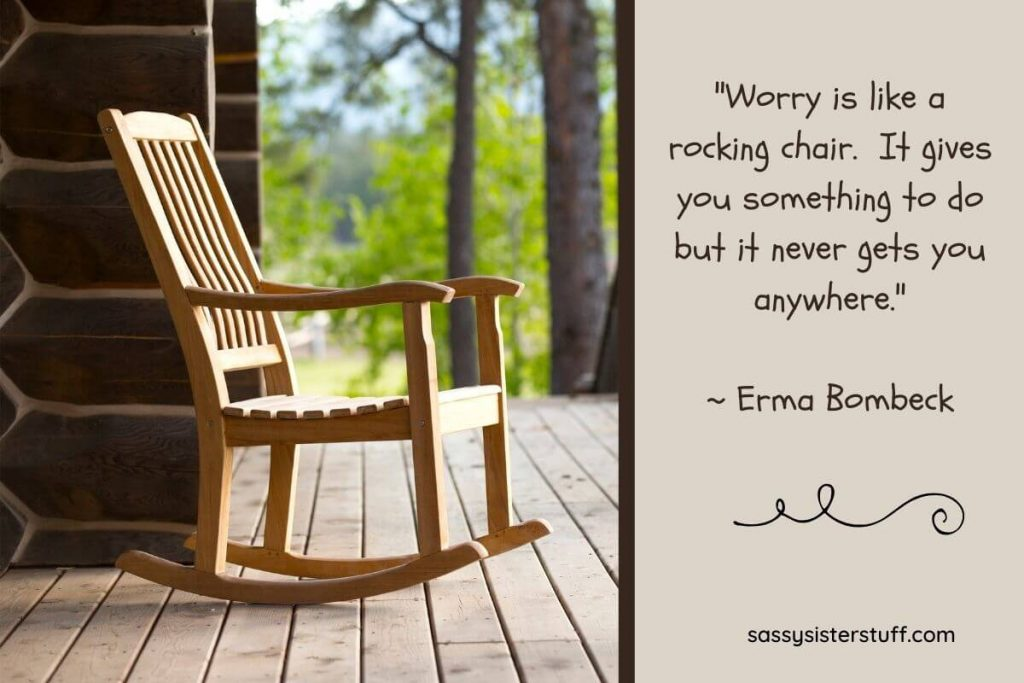 wooden rocking chair sitting on a log cabin porch with a quote about not worrying because it doesnt get you anywhere