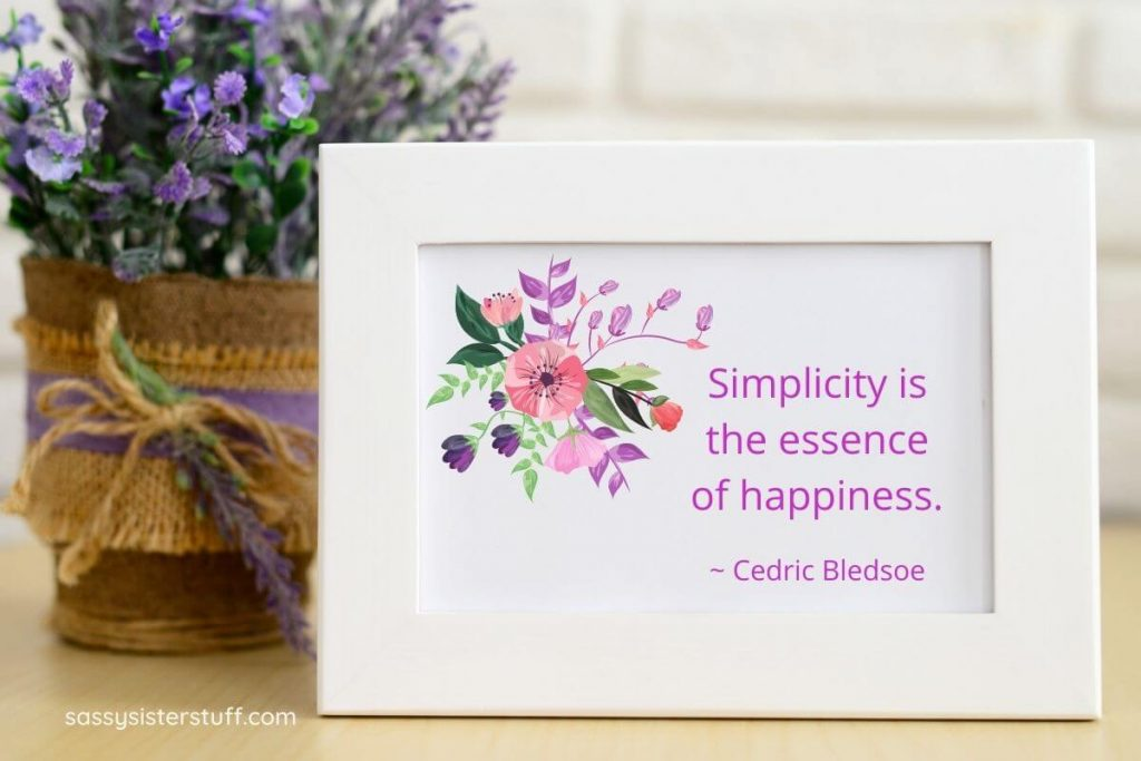a pot of purple flowers with a white framed quote about how to life a simple life and be happy